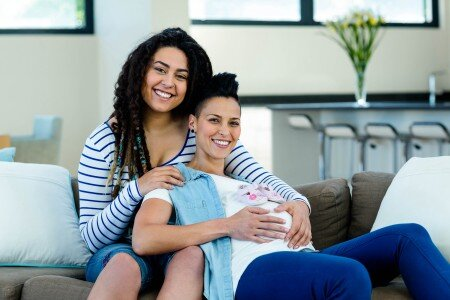 pregnant lesbian couple sitting on a sofa with a pair of pink baby shoes