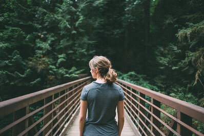 One woman looking ahead of herself on a bridge surrounded by nature