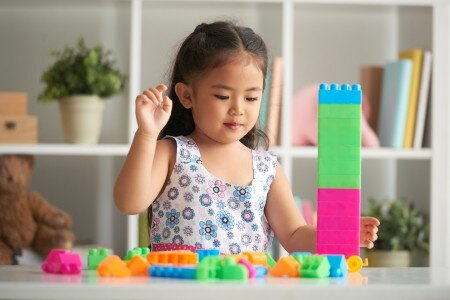 Small asian girl playing with duplo