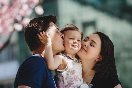 Family hugging their daughter