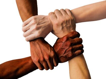 Multi-ethnic hands holding each other