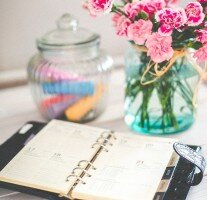 Calendar planner on a table with flowers in a vase