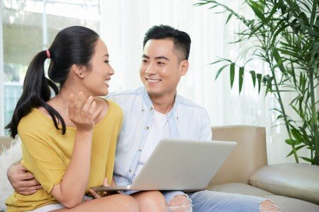 Happy asian couple looking at each other with a laptop on their lap